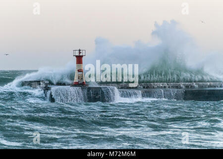Enormous waves seen crashing up against the breakwater of Kalk Bay harbour in Cape Town, South Africa. The waves - Stock Image