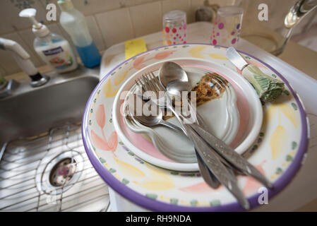 Dirty Dishes pile up next to kitchen sink. - Stock Image