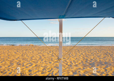 Awning structure for beach chair. Beach at sunset background - Stock Image