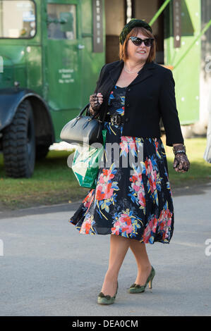 Chichester, West Sussex, UK. 14th Sep, 2013. Goodwood Revival. Goodwood Racing Circuit, West Sussex - Saturday 14th September. A lady in vintage clothing walks gracefully through the circuit. Credit:  MeonStock/Alamy Live News - Stock Image