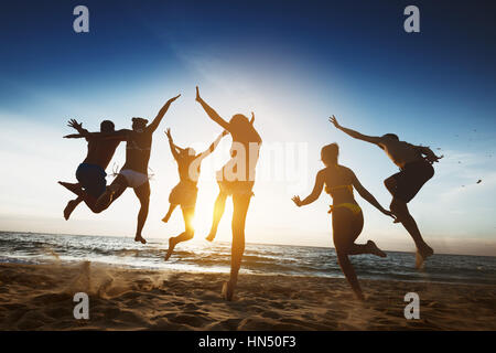Happy friends sunset jump friendship holidays - Stock Image