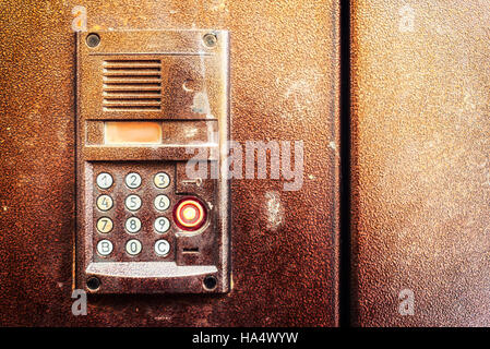Horizontal composition of an electronic door entry keypad in brown metal. - Stock Image
