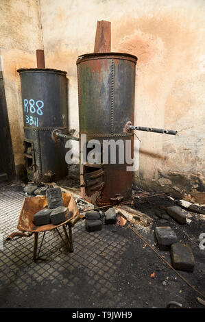 Interior of neglected facilities with rusty metal boilers and coal bricks at the Canfranc International railway station (Pyrenees,Huesca,Aragon,Spain) - Stock Image