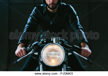 Young male motorcyclist straddling vintage motorcycle in garage, cropped front view - Stock Image