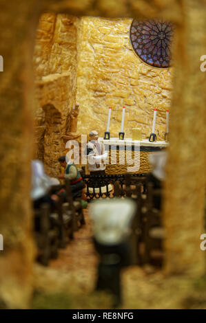 Creche figures and scenes made in Provence.  Here a Priest figurine in a church behind a window - Stock Image