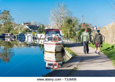 Hest Bank, Lancashire, UK, 10 April 2019. UK Weather: Clear blue sky and bright sunshine after an overnight frost as dog walkers make their way along the towpath by the Lancaster Canal. Further sunshine is forecast for the rest of the day, but with an Easterly breeze it will feel cool out of the sunshine. Credit Keith Douglas News/Alamy Live News - Stock Image