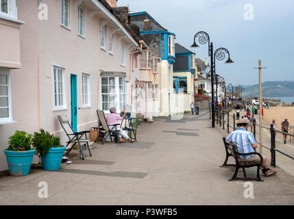 An artist works on her painting sitting outside cottages on Marine Parade in Lyme Regis, on the Jurassic Coast, Dorset, England - Stock Image