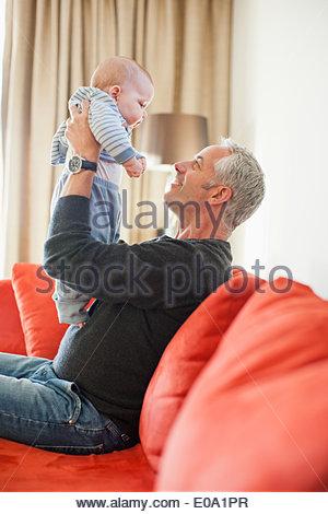 Man holding baby boy on lap - Stock Image