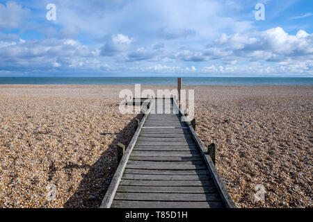 a long straight wooden decking pathway with a diminshing perspective on a pebble beach leading to the sea, the pathway starts large in the foreground  - Stock Image