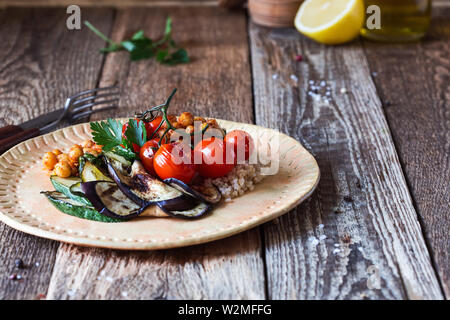 Healthy vegan meal. Veggie salad with grilled vegetables cherry tomatoes, eggplant, zucchini, quinoa, crispy crunchy roasted chickpeas on rural cerami - Stock Image