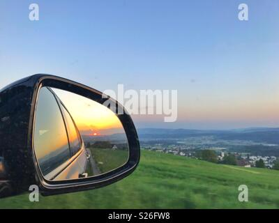 Sunset in the rear view mirror - Stock Image