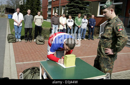 (dpa) - Conscipts in civilian clothes sign in to a list on a table before dressing at the Knuell barracks in Schwarzenborn, - Stock Image
