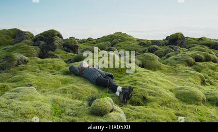 High angle view of woman laying in mossy field in remote rocky landscape under clear blue sky - Stock Image
