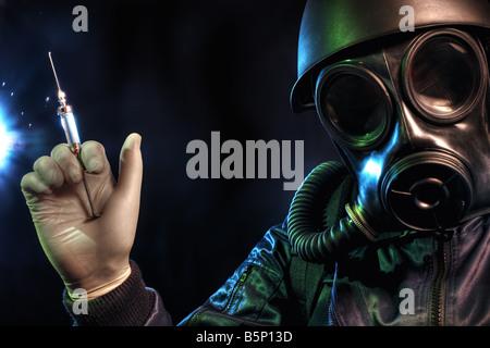 Gas masked man holding a syringe - Stock Image