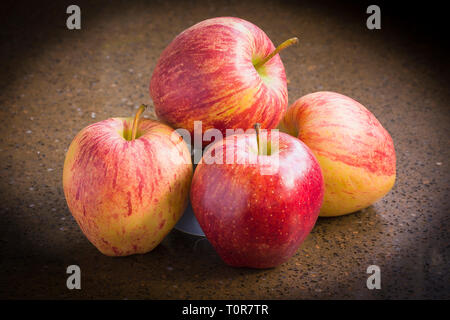 A group of four British-grown ripe red Cameo eating apples ready for eatingn - Stock Image