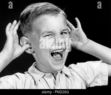 1950s BOY WAVING HANDS WITH THUMB IN EAR MOUTH OPEN TAUNTING MOCKING FACIAL EXPRESSION GESTURE SNEERING LOOKING AT CAMERA - j5012 CLE003 HARS EYE CONTACT PRETEEN BOY WEIRD HEAD AND SHOULDERS TEASE ZANY UNCONVENTIONAL GESTURES ANNOYING MOCK STYLISH IDIOSYNCRATIC SMART ALECK SNEER AMUSING ECCENTRIC JUVENILES MAKE FUN OF MOCKING NASTY PRE-TEEN PRE-TEEN BOY RUDE TAUNT TEASING BLACK AND WHITE CAUCASIAN ETHNICITY ERRATIC OLD FASHIONED - Stock Image