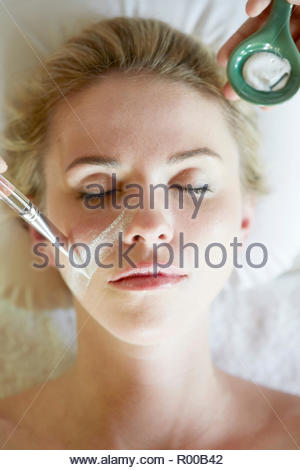 Young woman getting face painted with white paste - Stock Image