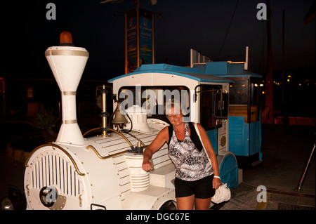 female enjoying holiday fun with sightseeing train - Stock Image