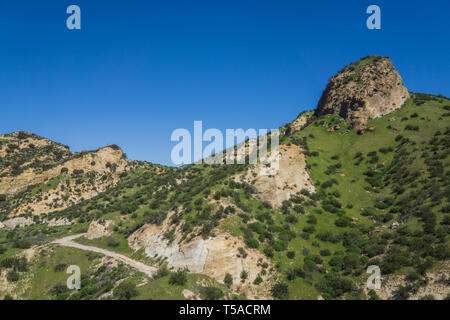 Hiking path leads along a hillside underneath a rock butte formation. - Stock Image