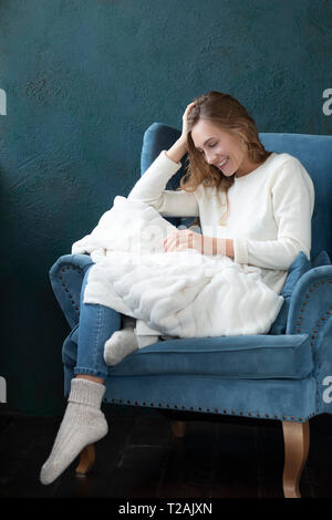 Smiling woman witting in armchair with white blanket - Stock Image