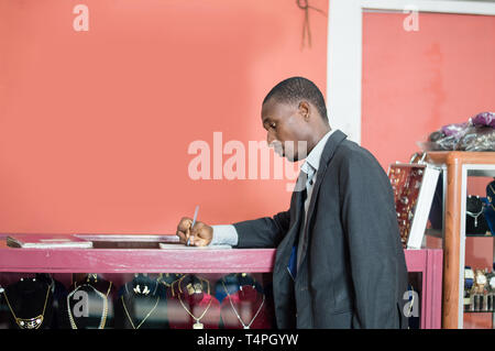 Young businessman signs a partnership agreement with the store owner. - Stock Image