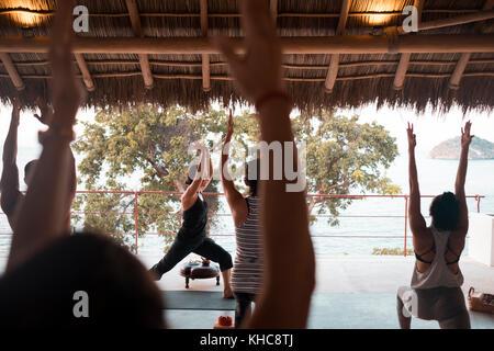 Group of multiple people practicing yoga on a palapa terrace. Yoga retreat Puerto Vallarta - Mismaloya, Mexico - Stock Image