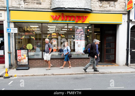 A Wimpy fast food restaurant on a busy High st in a town in England. The shop front and company logo are clearly shown as  pedestrians walk past - Stock Image