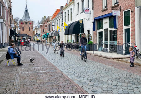 A young family on bicycles ride past a street musician playing accordion as a girl dances on Jufferenstraat in the old town of Elburg, Netherlands. - Stock Image