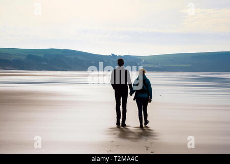 A couple holding hands walking together on a quiet sandy beach at low tide. Woolacombe, North Devon, England, UK, Britain - Stock Image