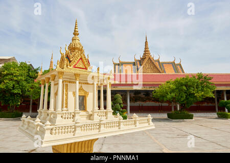A small shrine with the Throne Hall roof in the background.  Inside the Royal Palace complex in Phnom Penh, Cambodia. - Stock Image