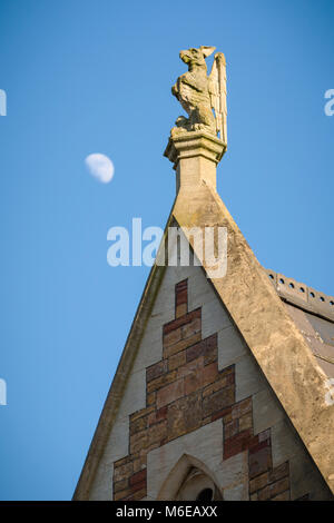 A sculptural finial in the shape of a Griffin (with dog-like attributes) on a Victorian building at Clifton College, - Stock Image