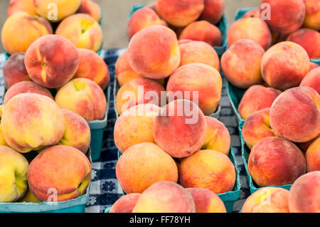 Photo of peaches in baskets on a table - Stock Image
