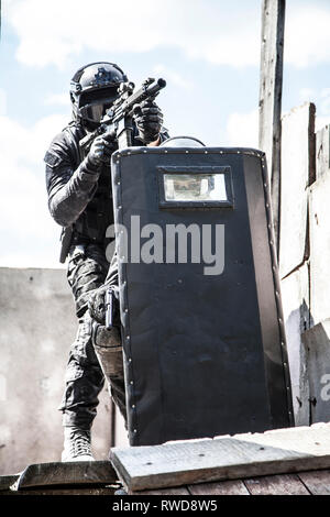 Spec ops police officers SWAT in black uniform in action. - Stock Image