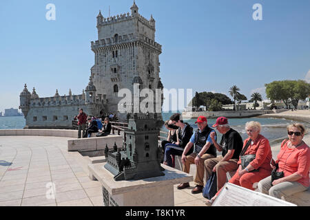Seniors tourists people couples visiting Belem Tower sitting outside by a miniature model replica of the building in Belem Lisbon Europe  KATHY DEWITT - Stock Image