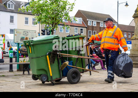 Street sweeper with his equipment hand cart clearing litter bins in Thirsk Market Place - Stock Image
