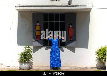 A young beautiful Indian woman model in a blue dress having fun and posing in front of the window of a Chinese cafe with graffiti artwork on the wall. - Stock Image