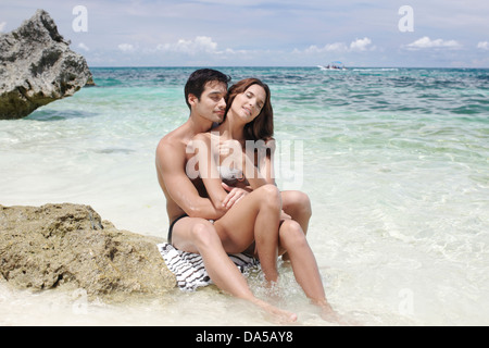 A couple embracing on a beach. - Stock Image
