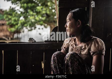 Khin San Htay, 25, at home in Gaung Gyi village after collecting emergency supplies provided by KMSS. Htay, a rice - Stock Image