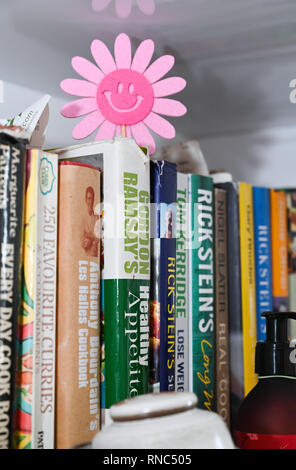 Celebrity chef cookery books on kitchen shelf  Photograph taken by Simon Dack - Stock Image
