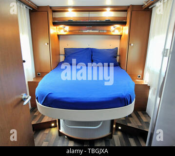 Bedroom Interior of Mobile Home with blue made up bed - Stock Image