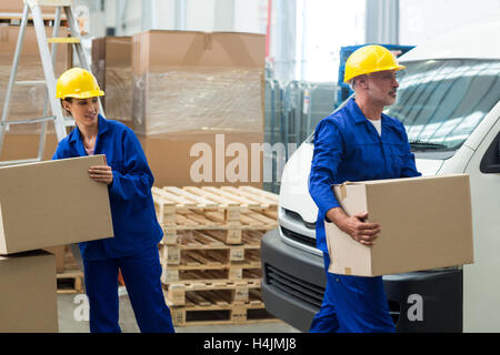 Delivery workers unloading cardboard boxes from pallet jack - Stock Image