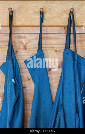 Three industrial aprons hanging on wooden pegs - Stock Image