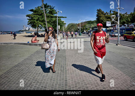 African American tourists couple strolling along Pattaya Beach Road, Thailand, Southeast Asia - Stock Image
