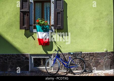 Italian national flag hanging from a open window shutters with bicycle. - Stock Image