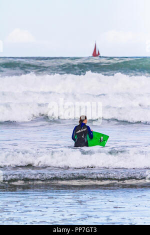 Bodyboarder entering the sea as a sailing boat passes along the horizon. Bamburgh, Northumberland. - Stock Image