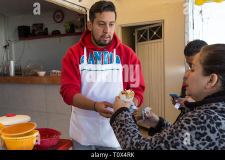 Young Mexican woman buying street tacos from a cafe in Santiago de Queretaro, Mexico - Stock Image