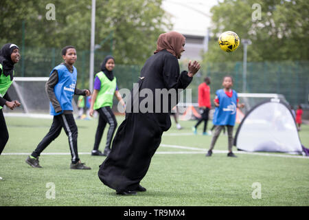 A Muslim mother playing football with children on an astroturf training pitch. - Stock Image