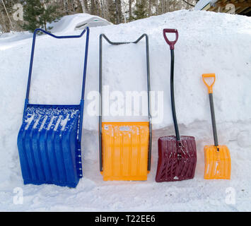A row of four shovels of various sizes, all needed during a winter in Quebec - Stock Image