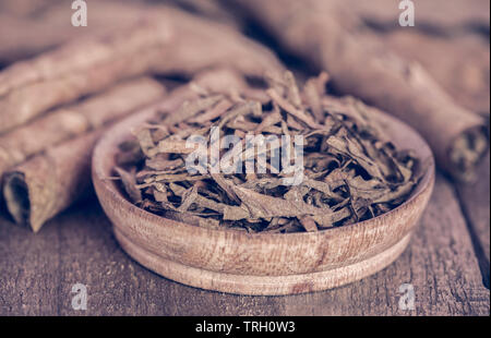 Rolled tobacco leaves and pieces in a wooden bowl - Stock Image