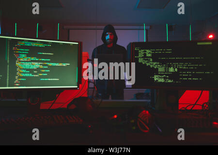 Serious young bearded hacker in hoodie standing in server room with computers and using laptop while getting into computer system - Stock Image